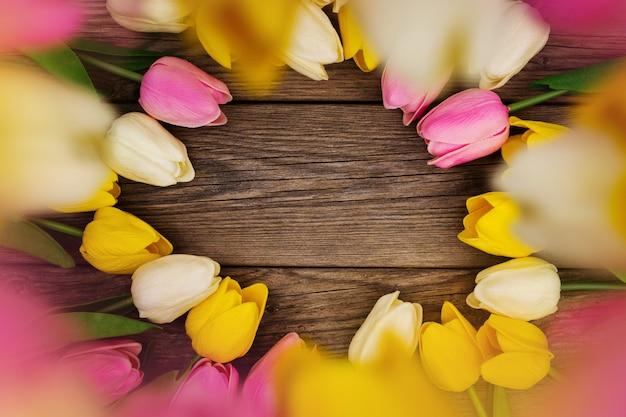 Bela composição com tulipas coloridas com espaço de cópia na madeira Foto gratuita