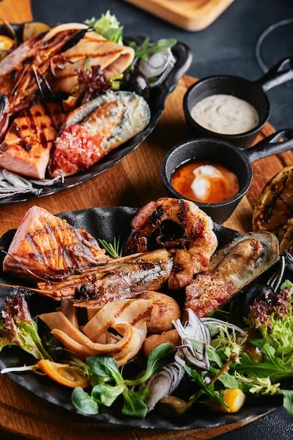 Bela composição sobre uma mesa de frutos do mar servida, lulas, camarões, filé de salmão e polvo. Foto Premium