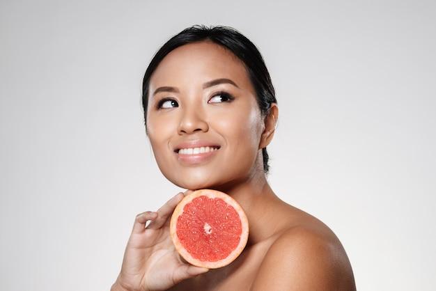 Bela dama asiática, olhando de lado e segurando a fatia de toranja perto do rosto Foto gratuita