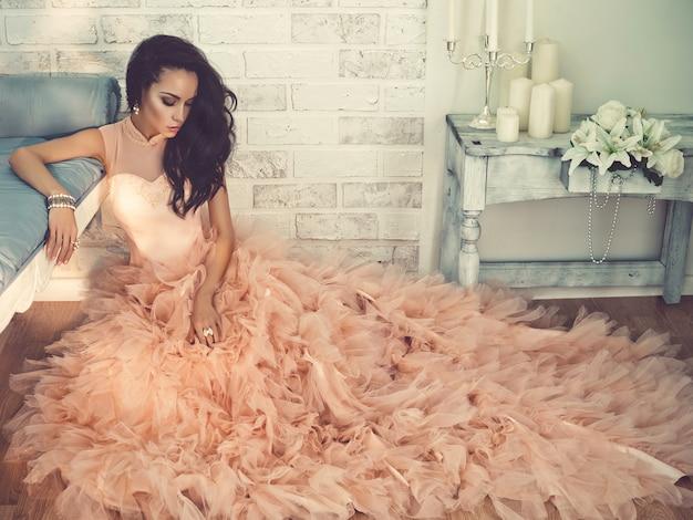 Bela dama em lindo vestido de alta costura sentado no chão Foto Premium