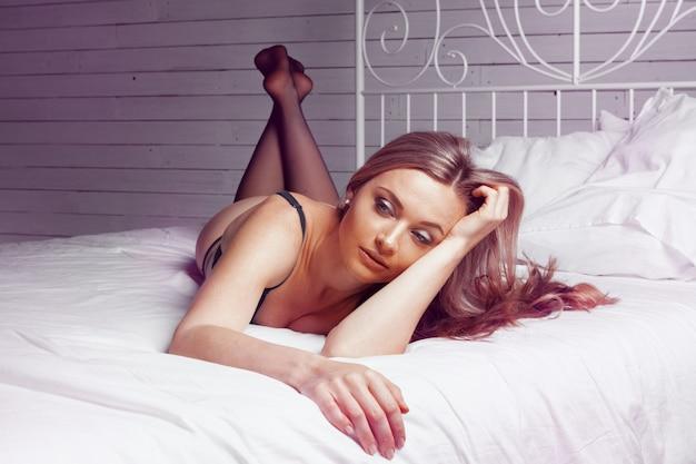Bela dama sexy calcinha preta elegante e meias na cama Foto Premium