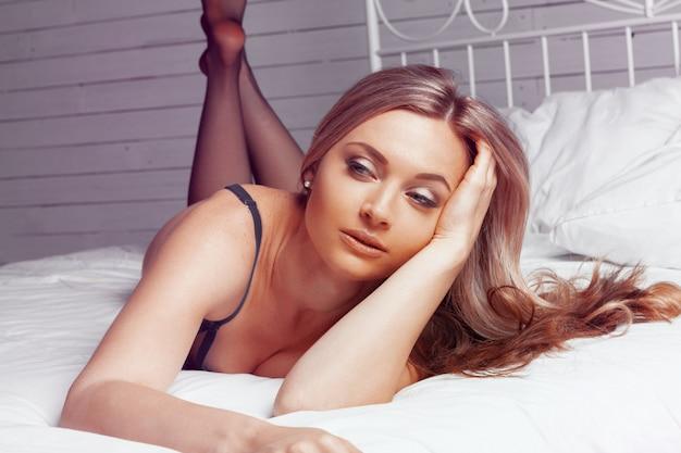 Bela dama sexy elegante calcinha preta e meias na cama Foto Premium