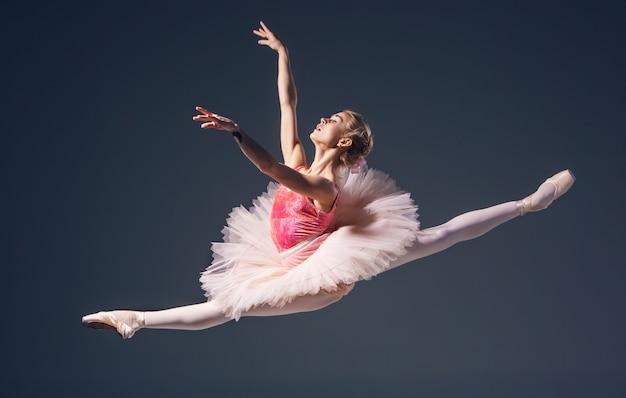 Bela dançarina de balé feminina em um fundo cinza Foto gratuita