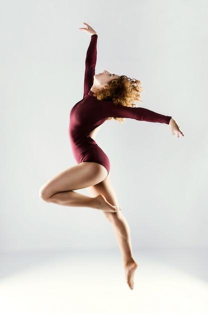 Bela dançarina profissional bonita que dançam sobre o fundo branco. Foto Premium