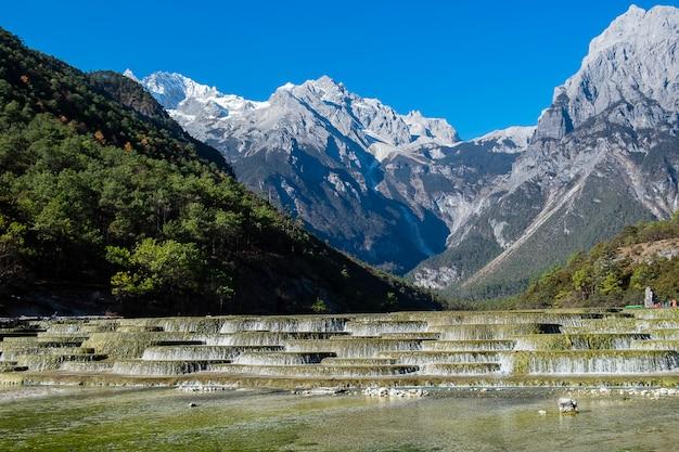 Bela do vale da lua azul, ponto de referência e local popular para atrações turísticas dentro da área cênica da montanha de neve do dragão de jade (yulong), perto da cidade velha de lijiang. lijiang, yunnan, china Foto Premium
