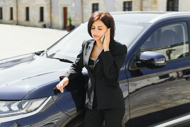 Bela empresária está falando no telefone celular e sorrindo em pé perto de seu carro e olhando para a frente com alegria Foto Premium