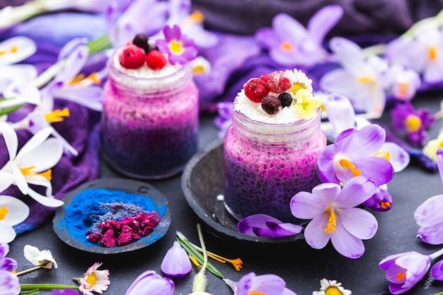 Bela exibição de vitaminas veganas roxas adornadas com flores coloridas Foto gratuita