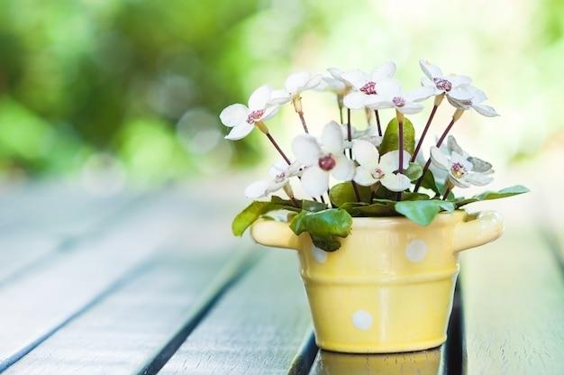 Bela flor artificial pote de decoração em cima da mesa para cartão Foto gratuita
