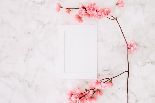 Bela flor de cerejeira sakura na primavera perto da moldura branca vazia no plano de fundo texturizado Foto gratuita