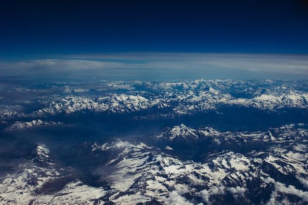 Bela foto aérea de um cenário montanhoso nevado sob o céu azul de tirar o fôlego Foto gratuita