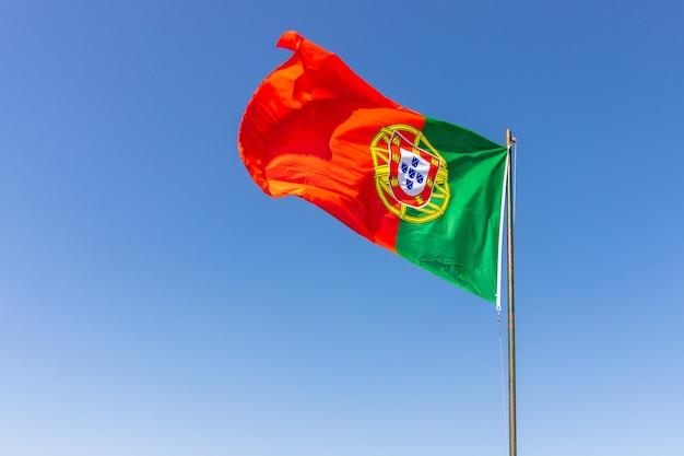 Bela foto da bandeira portuguesa balançando no céu calmo e brilhante Foto gratuita