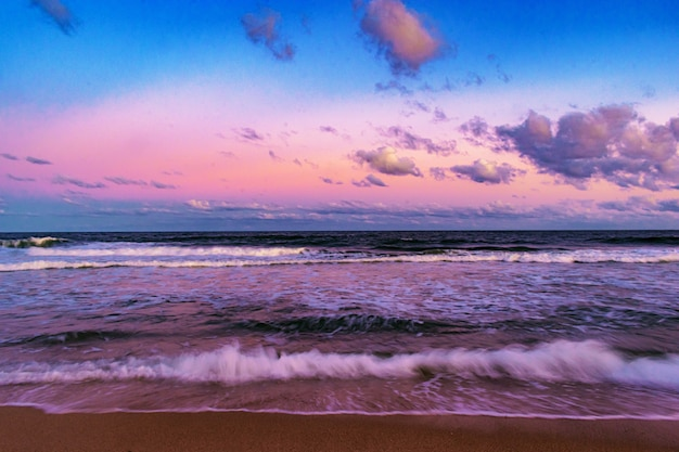 Bela foto da paisagem do pôr do sol na praia com um céu nublado ao fundo Foto gratuita