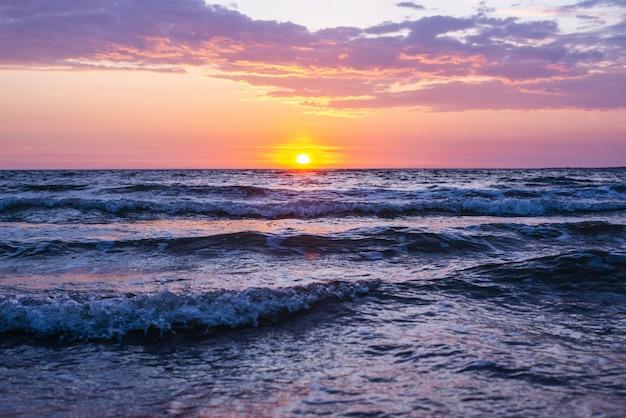 Bela foto das ondas do mar sob o céu rosa e roxo com o sol brilhando durante a hora de ouro Foto gratuita