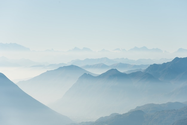 Bela foto de altas colinas brancas e montanhas cobertas de nevoeiro Foto gratuita