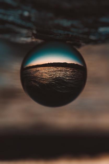 Bela foto de close-up vertical de uma bola de vidro com o reflexo do pôr do sol de tirar o fôlego Foto gratuita