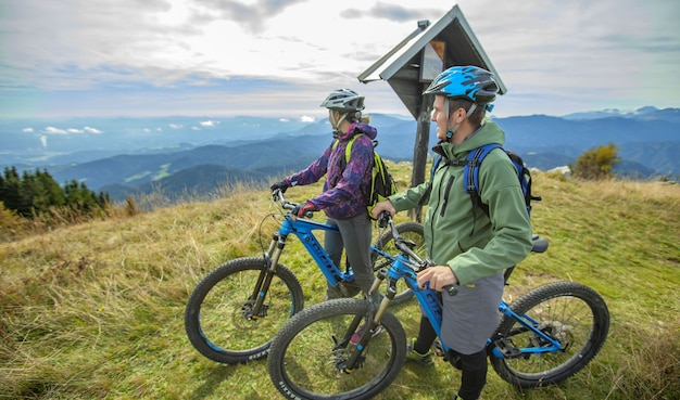 Bela foto de dois ciclistas em pé olhando as maravilhas da natureza Foto gratuita