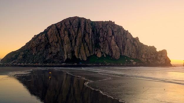 Bela foto de falésias rochosas perto de uma praia com luz solar do lado Foto gratuita