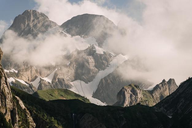 Bela foto de montanhas verdes cobertas por nuvens brancas em um céu azul claro Foto gratuita