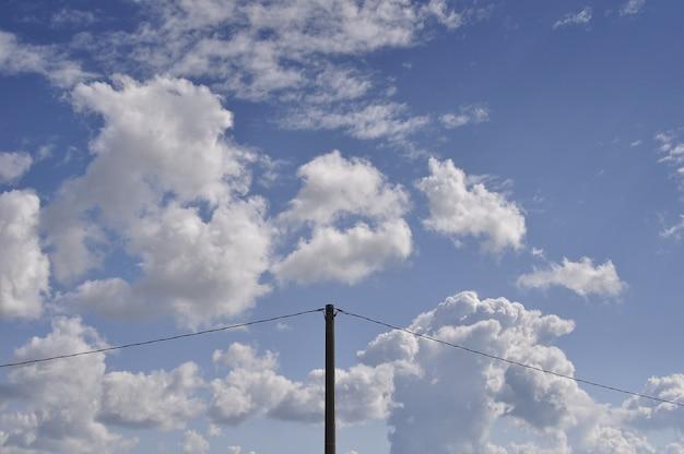 Bela foto de nuvens brancas no céu azul com um poste de eletricidade no meio Foto gratuita
