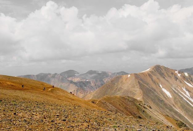 Bela foto de pessoas subindo a montanha à distância sob um céu nublado Foto gratuita