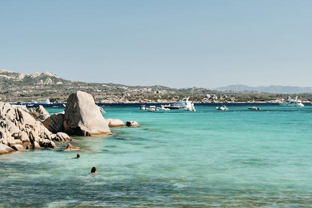 Bela foto de rochas na água com barcos e montanhas ao longe sob um céu azul Foto gratuita