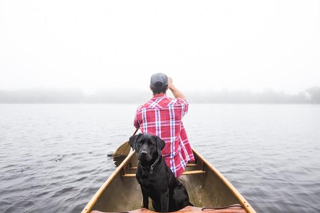 Bela foto de um cão preto e um macho navegando em um pequeno barco no corpo de água Foto gratuita