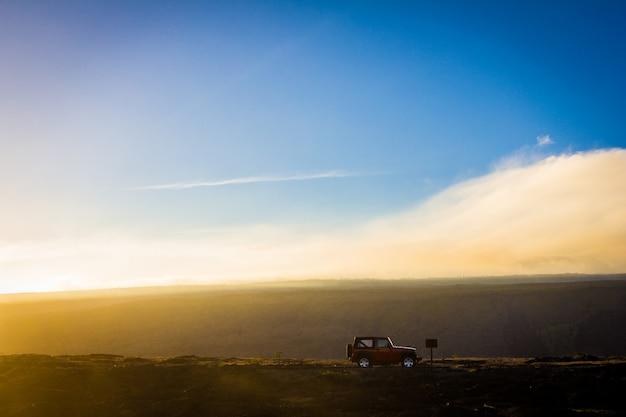 Bela foto de um carro offroad em uma colina com um céu azul ao fundo durante o dia Foto gratuita