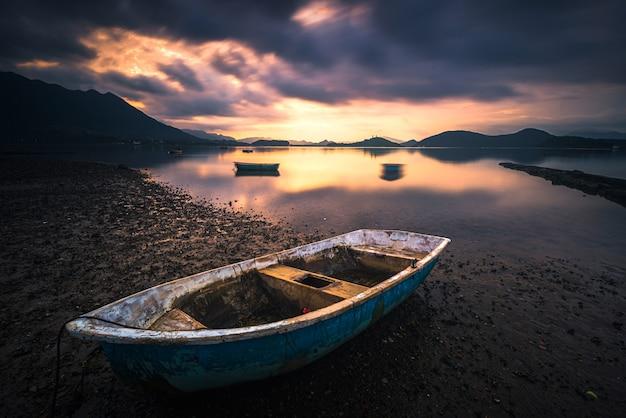 Bela foto de um pequeno lago com um barco a remo de madeira em foco e nuvens surpreendentes no céu Foto gratuita