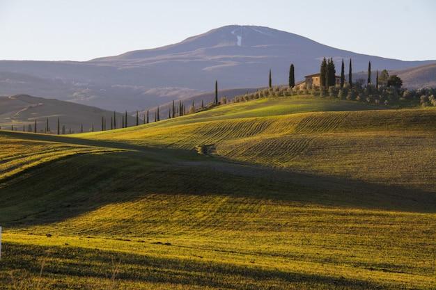 Bela foto de uma casa de campo no meio de um campo cercado por colinas sob o céu claro Foto gratuita