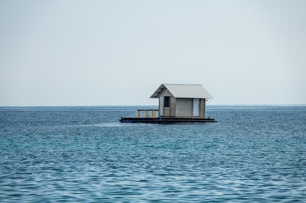 Bela foto de uma casa flutuante em um oceano azul com um céu claro e branco no Foto gratuita