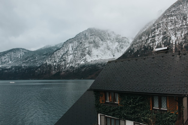 Bela foto de uma casa perto do lago e montanhas cinzentas cobertas de neve durante o dia Foto gratuita