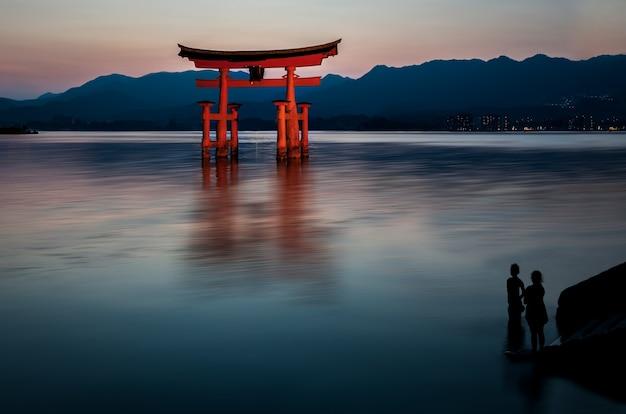 Bela foto de uma construção vermelha na água com silhuetas humanas olhando para ele Foto gratuita
