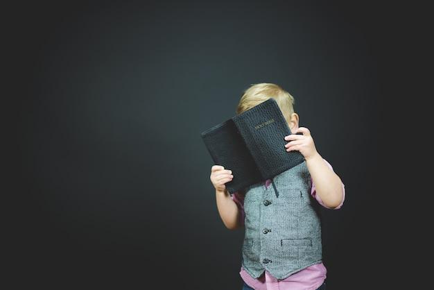 Bela foto de uma criança segurando uma bíblia aberta Foto gratuita