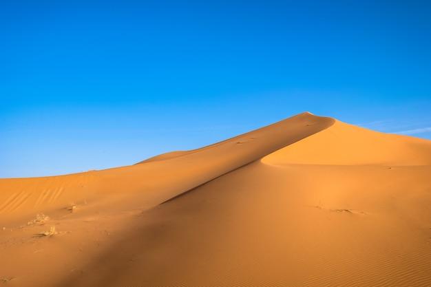 Bela foto de uma duna de areia com um céu azul claro Foto gratuita