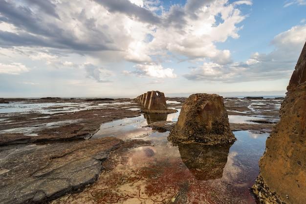 Bela foto de uma formação rochosa marrom, rodeada pela água do oceano sob o céu nublado Foto gratuita