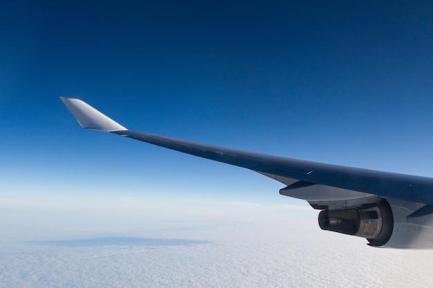 Bela foto de uma janela de avião das asas sobre as nuvens Foto gratuita
