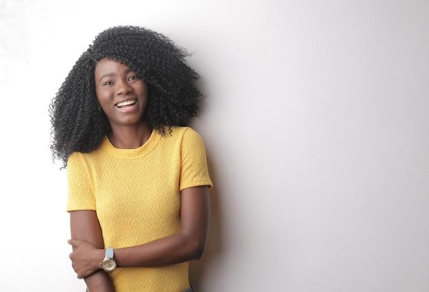 Bela foto de uma jovem mulher com cabelos cacheados isolados em um fundo cinza Foto gratuita