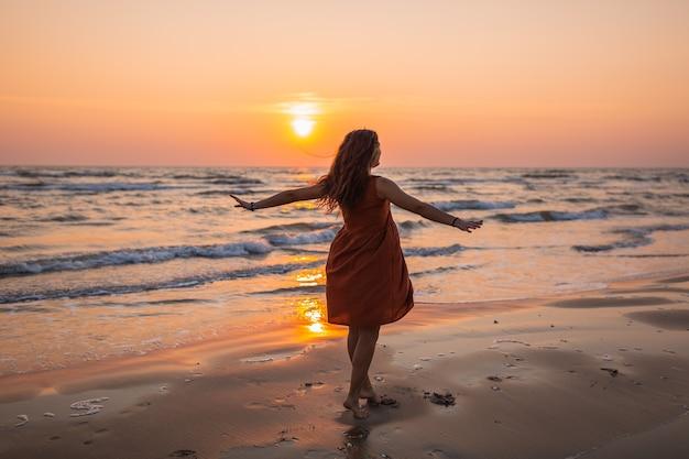 Bela foto de uma modelo com um vestido de verão marrom apreciando o pôr do sol na praia Foto gratuita