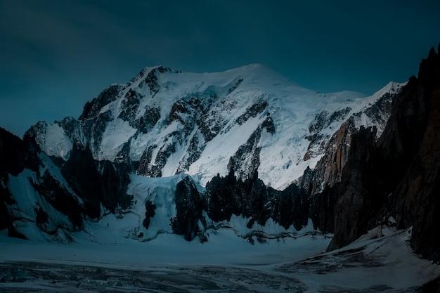Bela foto de uma montanha de neve com um céu azul escuro Foto gratuita