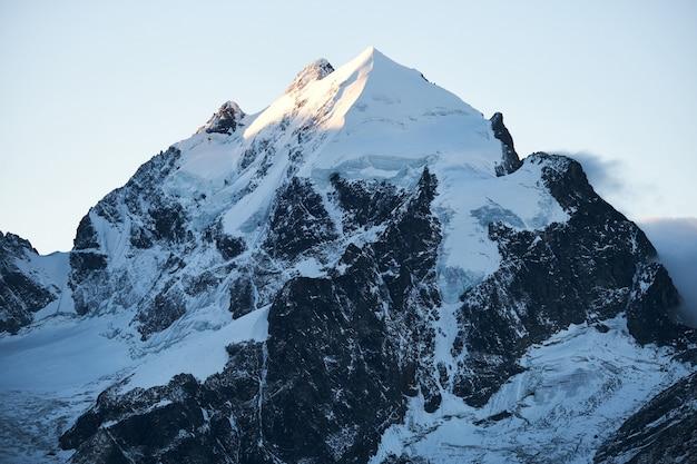 Bela foto de uma montanha de neve com um céu claro durante o dia Foto gratuita