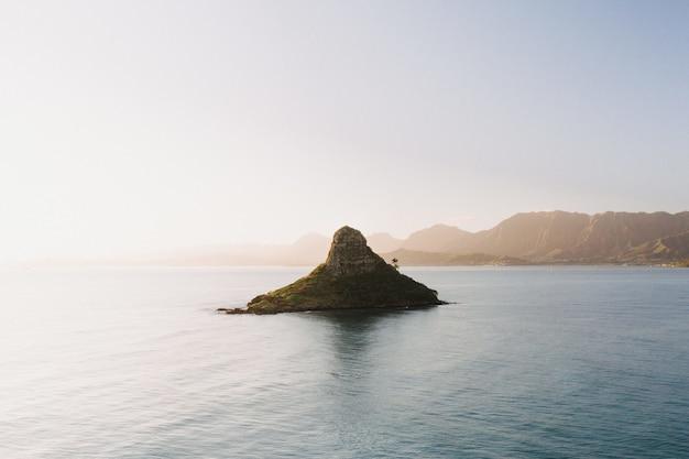 Bela foto de uma pequena ilha no centro do mar aberto com um cenário do nascer do sol Foto gratuita