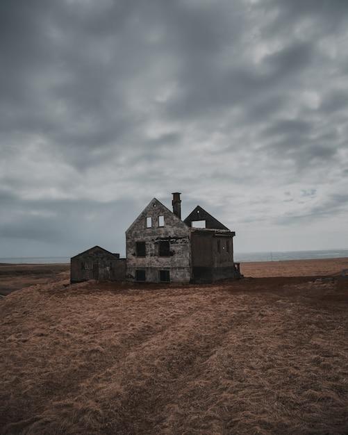 Bela foto de uma velha casa abandonada e meio destruída em um grande brownfield sob o céu cinzento Foto gratuita