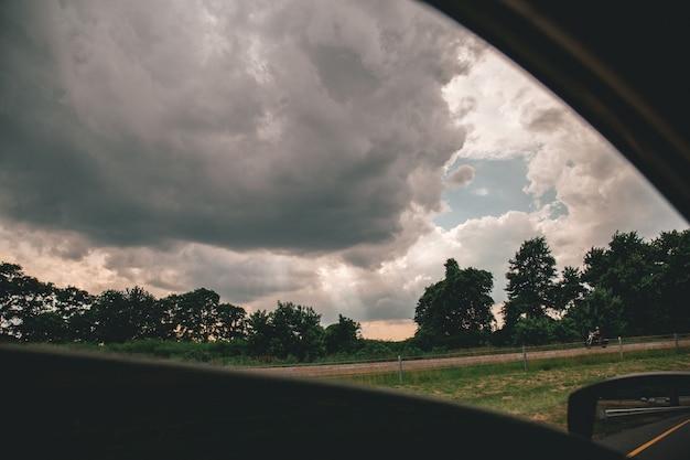 Bela foto do céu nublado acima de árvores tiradas de um carro Foto gratuita