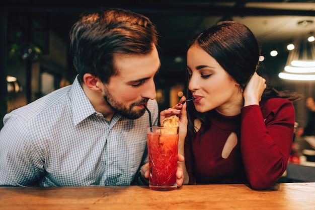 Bela foto do jovem casal sentados juntos e bebendo um coquetel vermelho no mesmo copo ao mesmo tempo. eles parecem felizes juntos. Foto Premium