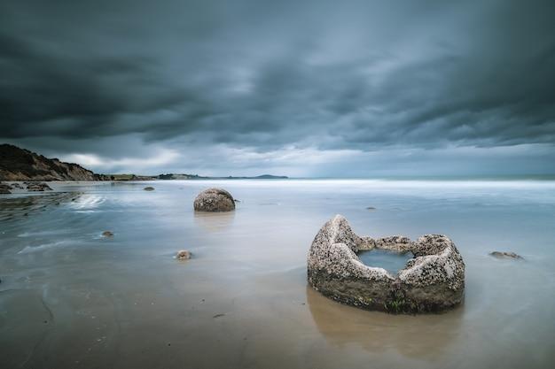 Bela foto do mar com pedras e montanhas ao longe sob um céu azul nublado Foto gratuita