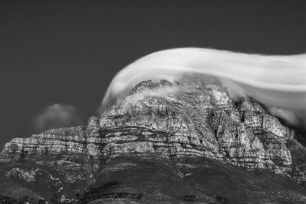Bela foto em escala de cinza de um penhasco rochoso coberto por nuvens de tirar o fôlego Foto gratuita
