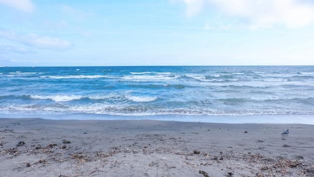 Bela foto grande de uma praia arenosa com incríveis ondas do mar e céu azul Foto gratuita