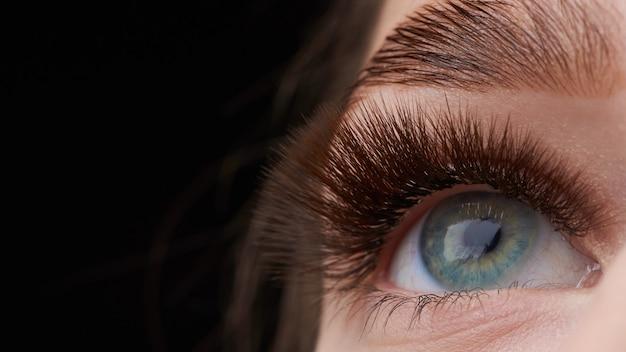 Bela fotografia macro do olho de uma mulher com maquiagem extrema de cílios longos Foto Premium