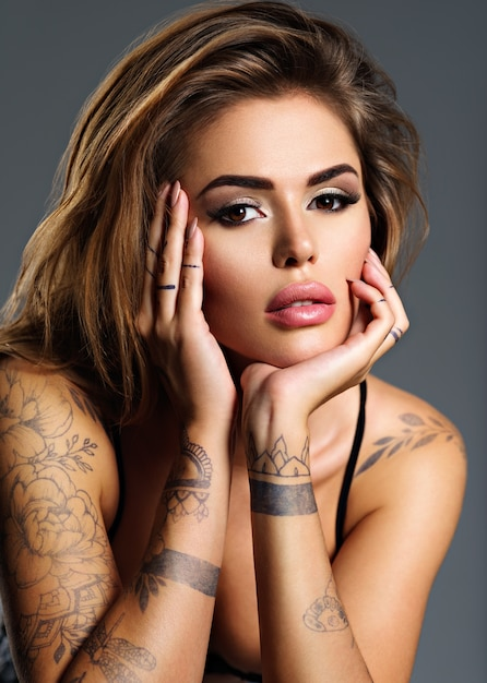 Bela garota sexy com uma tatuagem no corpo. retrato de uma jovem mulher atraente adulta com cabelo castanho. Foto gratuita