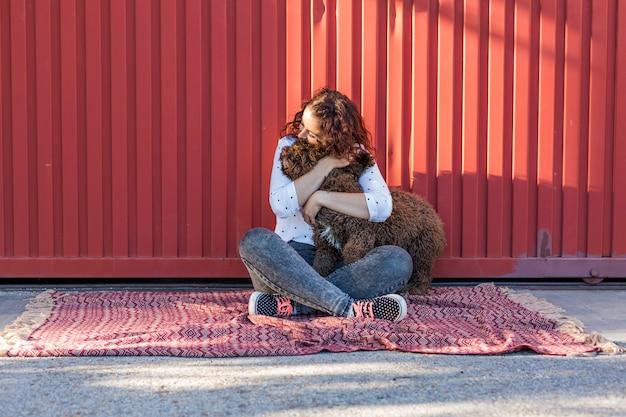Bela jovem abraçando seu cachorro, um cão de água marrom espanhol Foto Premium